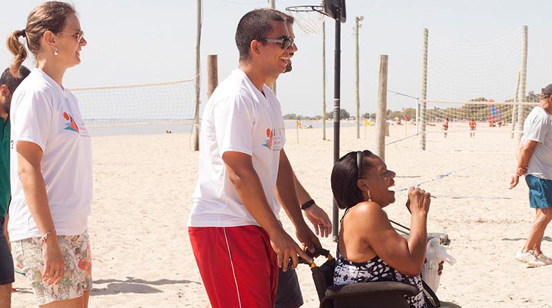 Funcionário da prefeitura conduzindo cadeirante na praia