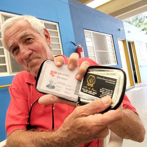 Um idoso feliz mostra sua carteira aberta com a credencial do projeto