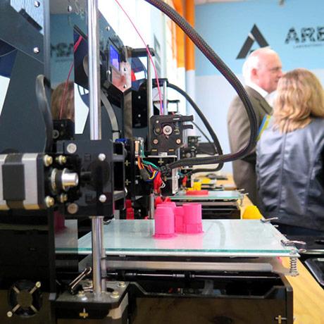 Uma impressora 3D em funcionamento com duas pessoas ao fundo conversando