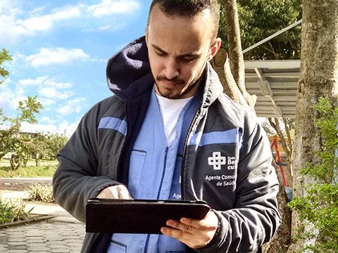 Uma pessoa uniformizada como agente da saúde utilizando um tablet