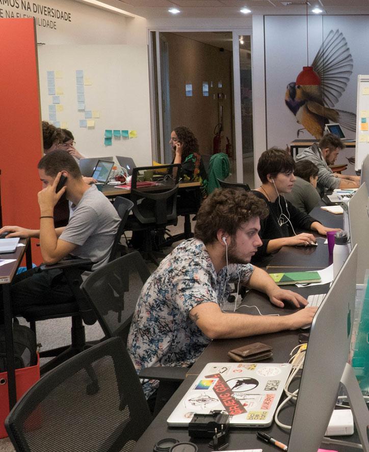 Consultores sentados trabalhando, alguns com notebook, fone de ouvido, atendendo telefone