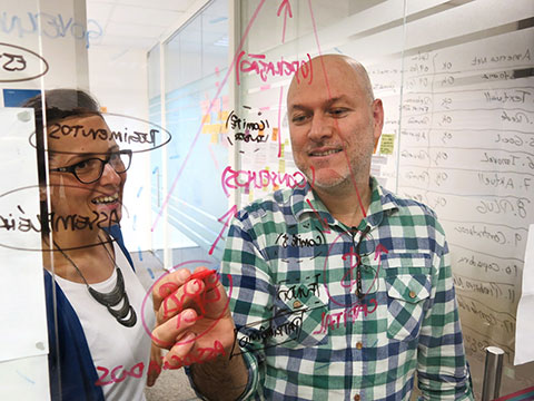 Duas pessoas traçando estratégias em um vidro transparente