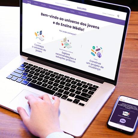 Um notebook e um celular na mesa com o site do projeto