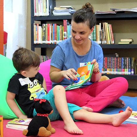 Uma jovem mostra um livro infantil para uma criança, ambos sentados no tapete