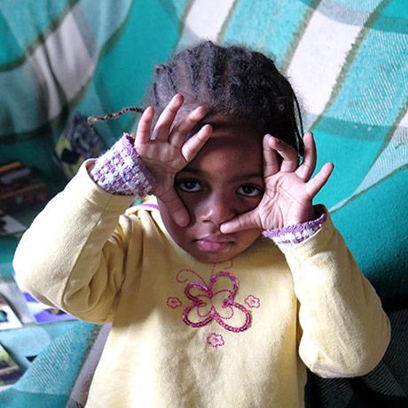 Uma criança com as mãos no rosto, sem cobrir os olhos